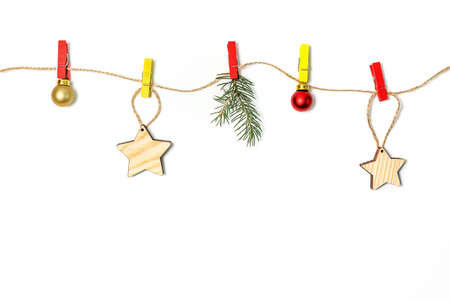 Christmas and new year holiday composition. Christmas decorations hang on colored clothespins on a rope white background. copy space.