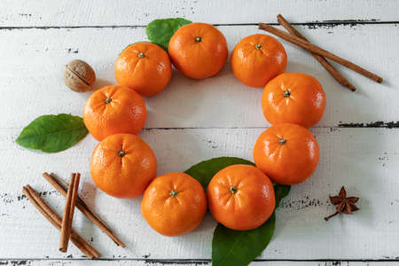Tangerines with leaves in the form of a Christmas wreath with cinnamon sticks and anise on a background of white wooden boards. The view from the top. Christmas cards and decorations.