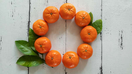 Tangerines with leaves in the form of a Christmas wreath on a background of white wooden boards.