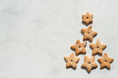 Christmas homemade shortbread cookies in the shape of a star of different sizes, on a white worn background. the view from the top. hard sunlight