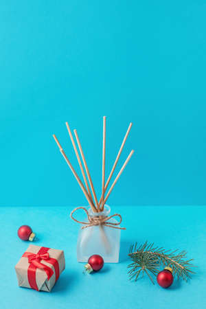 home fragrance in a glass diffuser with wooden sticks on a blue background. Christmas and new year atmosphere 스톡 콘텐츠
