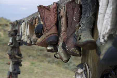 fray: These wonderfully display boots are serving a purpose long after there time  So many pair mounted upon a constructed rail  Stock Photo