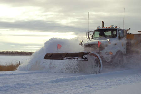 Snow plow in early morning on rural road after winter storm photo