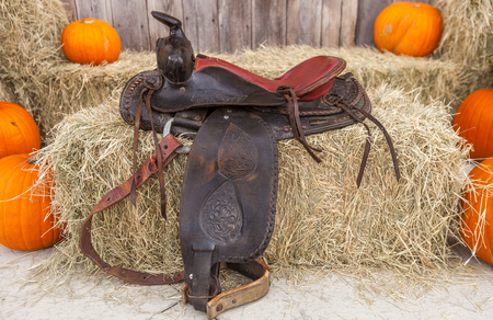Leather saddle on hay bales surrounded by pumpkins