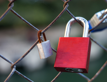 lock symbol: Red love lock attached to wire fence next to a rusty lock Stock Photo