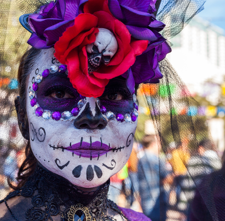 SAN ANTONIO, TEXAS - OCTOBER 28, 2017 - Woman wears face paint and headdress for Dia de Los MuertosDay of the Dead celebration. Day of the Dead is a Mexican holiday celebrated throughout Mexico, in particular the Central and South regions, and by people