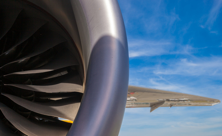 Close up section of jet engine with titanium blades and section of the wing on a blue sky background