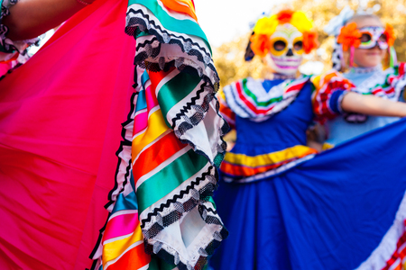 Close up detail of traditional dress and blurred background of girls with masks attending Dia de los MuertosDay of the Dead celebration