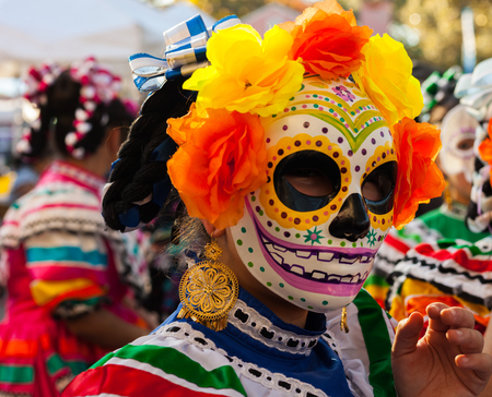 Young woman wearing colorful skull mask and paper flowers for Dia de Los MuertosDay of the Dead