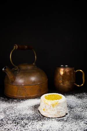 Lemon cake with powdered sugar on dark background with antique copper tea pot and mug Stock Photo