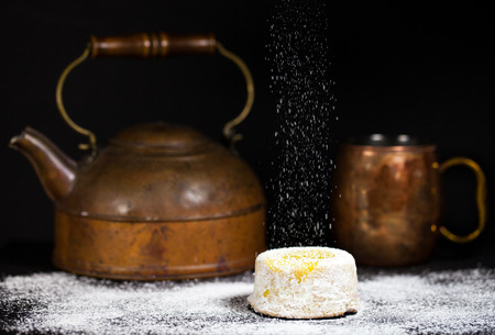 Lemon cake with powdered sugar drizzle on dark background with antique copper tea pot and mug