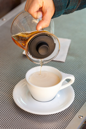 Woman hand pours black tea from glass teapot into ceramic white cup