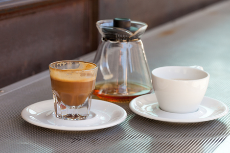 Consumed cortado coffee in a glass with caeramic white cup and teapot on metallic table and a rusty background
