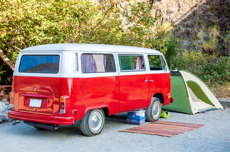 Beach campsite with red hippie minibus, green tent and rustic rughippie lifestyle concept