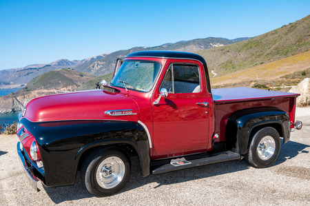MONTEREY, CALIFORNIA - SEPTEMBER 10, 2015 - Bright red and black classic Ford F-100 parked on the shore of the Pacific ocean, on the famous Pacific Coast Highway.