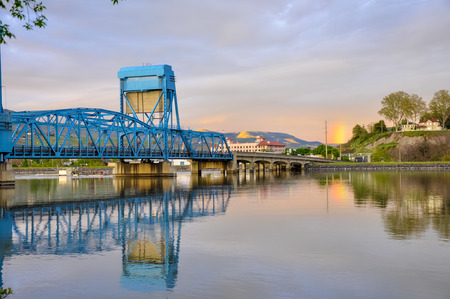 Lewiston - Clarkston blue bridge reflecting in the Snake River against evening sky
