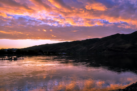 Dramatic sunset landscape with lake, sky reflection, fishing boat and foothills