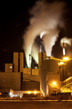 Paper mill factory with heavy smoke from production coming out of the chimneys Stock Photo
