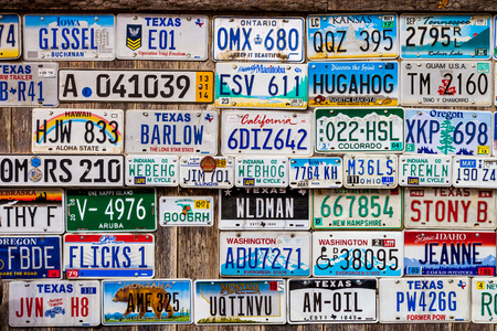 LUCKENBACH, TX - JANUARY 11, 2018 - Various old license plates displayed on a wooden wall. Redactioneel