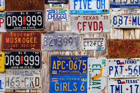 LUCKENBACH, TX - JANUARY 11, 2018 - Various old license plates displayed on a wooden wall. Stockfoto - 117819246