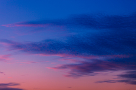Pink and purple sunset sky with clouds painted in dark tones of blue