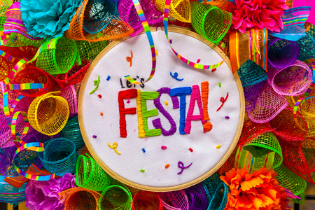 The word fiesta stitched in colorful letters on multicolored mash decorated with glitter and paper flowers Stock Photo