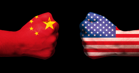 Flags of USA and China on two clenched fists facing each other on black backgroundusa china trade war concept