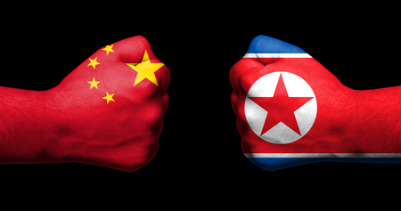 Flags of China and North Korea painted on two clenched fists facing each other on black Stock Photo