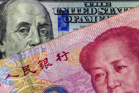 Cierre de billetes de 100 yuanes sobre billetes de cien dólares con enfoque en retratos de Benjamin Franklin y Mao Tse-tung / concepto de guerra comercial entre Estados Unidos y China