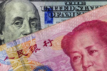 Schließen Sie oben von 100 Yuan-Banknote über einer hundert-Dollar-Banknote mit Fokus auf Porträts von Benjamin Franklin und Mao Tse-tung / USA gegen China-Handelskriegskonzept