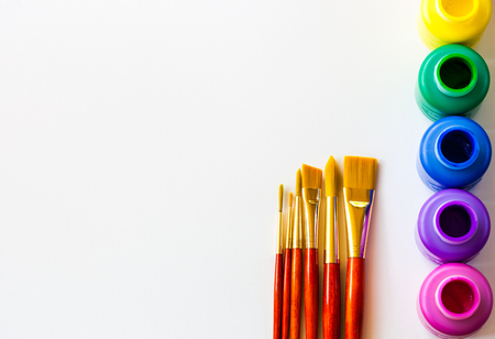 Colorful paint bottels and paint brushes on white background with copy space, top viewarts and crafts background concept