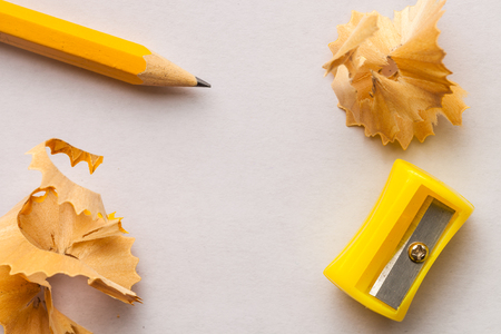Yellow pencil, sharpner and shavings on white paper background with copy space