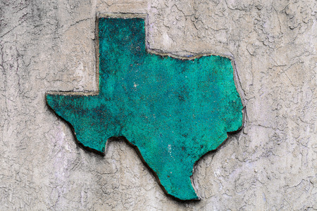 Texas shaped grunge rough textured concrete decoration on stone wall