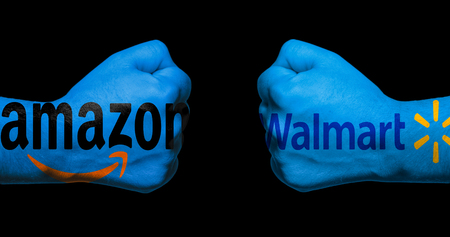 SAN ANTONIO, TX - APRIL 9, 2018 - Amazon and Walmart logos painted on two clenched fists facing each other/concept of retail war between Amazon and Walmart Editorial