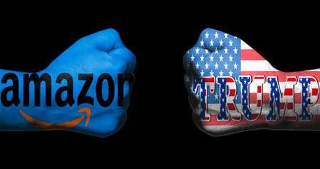 SAN ANTONIO, TX - APRIL 9, 2018 - Amazon logo and Trump with US flag painted on two clenched fists facing each otherconcept of conflict between Trump and Amazon
