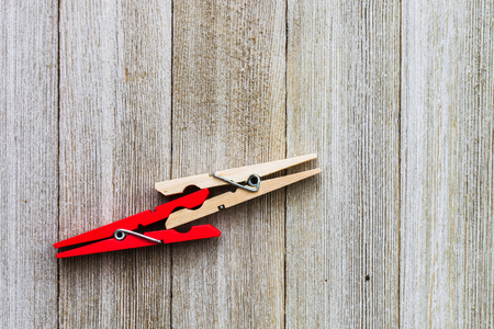 Two clothespins, on red and ordinary colored on a wooden backgroundabstract cooperation, teamwork concept 版權商用圖片