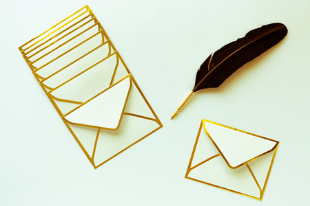 Envelopes with golden edges and quill pen on on white background with copy space, wedding mock up concept