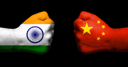 Flags of India and China painted on two clenched fists facing each other on black background/India - China relations concept Foto de archivo