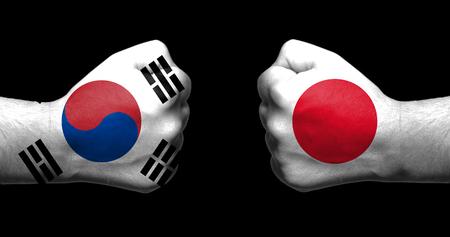 Flaggen von Japan und Südkorea gemalt auf zwei geballten Fäusten, die sich auf schwarzem Hintergrund gegenüberstehen / Japan - Südkorea-Beziehungskonzept Standard-Bild