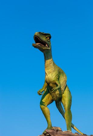 Model of Velociraptor roaring against blue sky Stock Photo