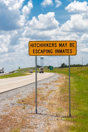 Highway warning sign about hitchhikers that might escaping inmates