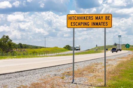 Highway warning sign about hitchhikers that might be escaping inmates Stock Photo