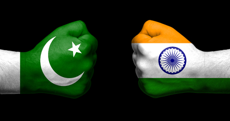 Flags of India and Pakistan painted on two clenched fists facing each other on black backgroundIndia - Pakistan relations concept Stock Photo