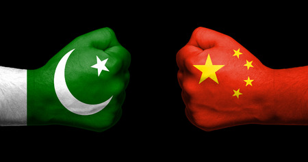 Flags of Pakistan and China painted on two clenched fists facing each other on black background/Pakistan - China relations concept 版權商用圖片