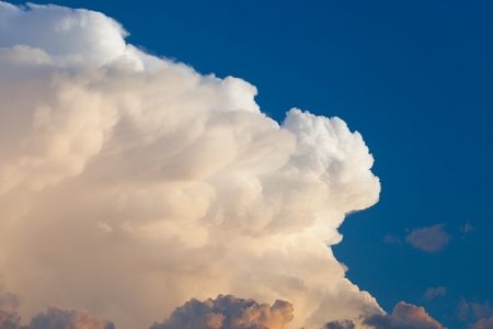 Towering cumulonimbus thunderstorm cloud with blue sky in the background Stock Photo