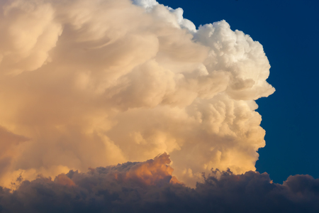 Towering cumulonimbus thunderstorm cloud with blue sky in the background