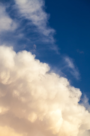 View of cumulonimbus thunderstorm cloud and cirrus cloud with blue sky in the background