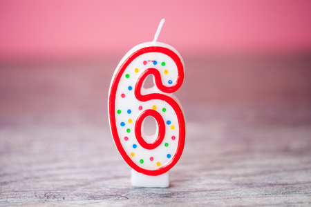 Colorful number 6 birthday cake candle on a pink background