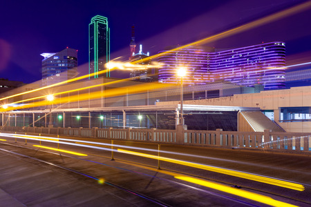 Light trails from moving streetcar on the Houston Street with the city of Dallas in background