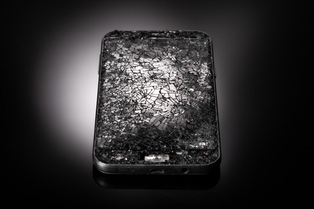 Smarthphone with crushed screen into pieces on a black reflective surface, studio shot / Destroied equipment